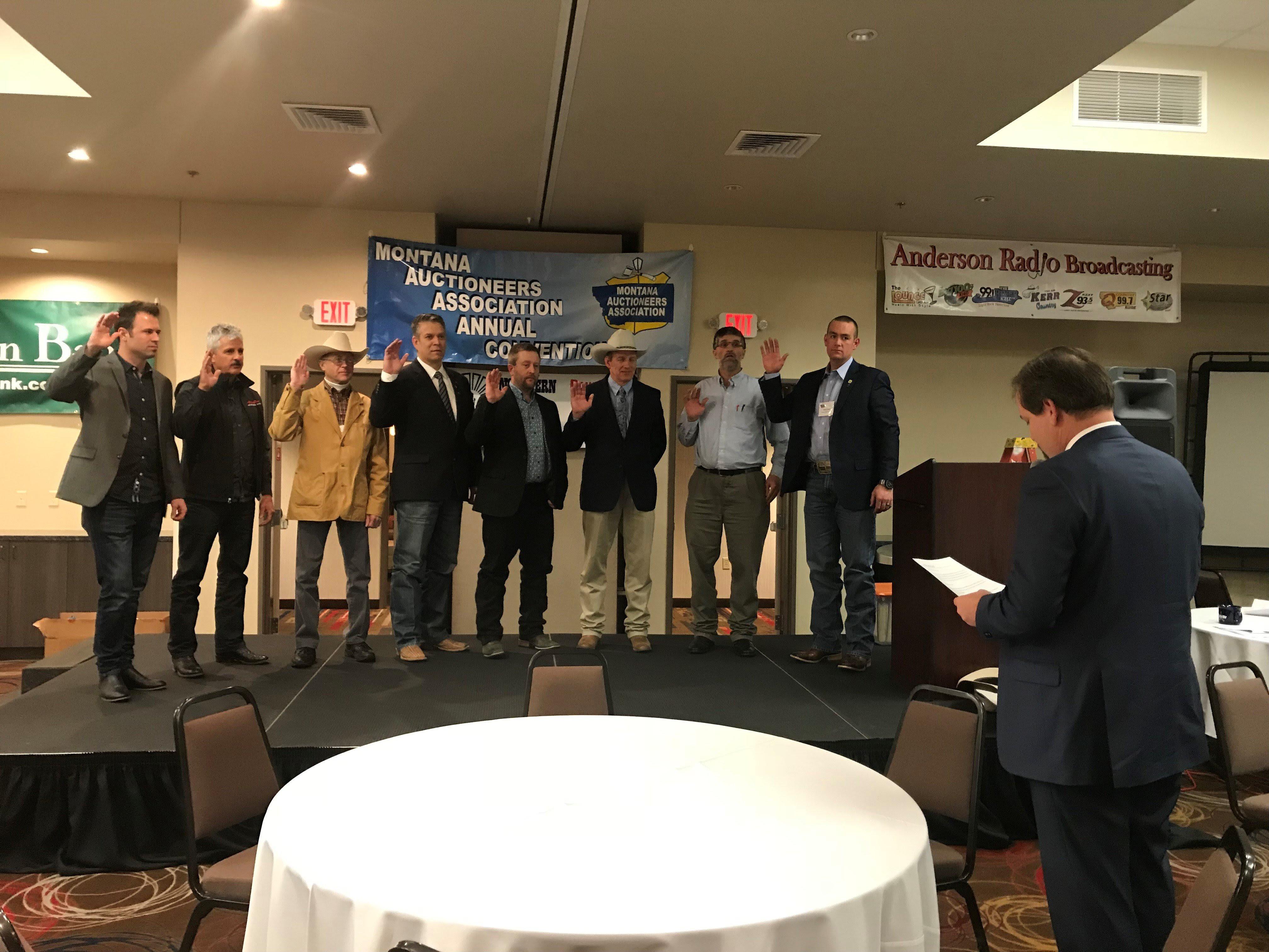 Tim Mast swears in the 2019 Montana Auctioneer Board of Directors. Left to right: Wade Affleck, Merton Musser, Robert McDowell III, JK Kinsey, Brian Young, Kevin Hill, Gideon Yutzy and Reed Tobol